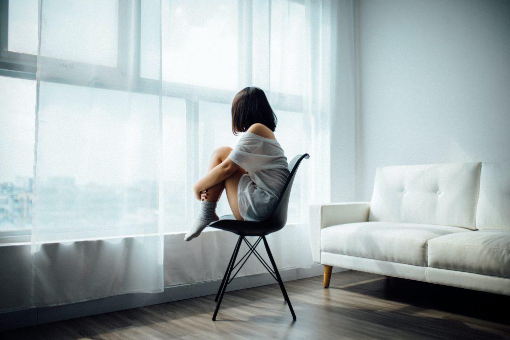 Dame som sitter alene på en stol