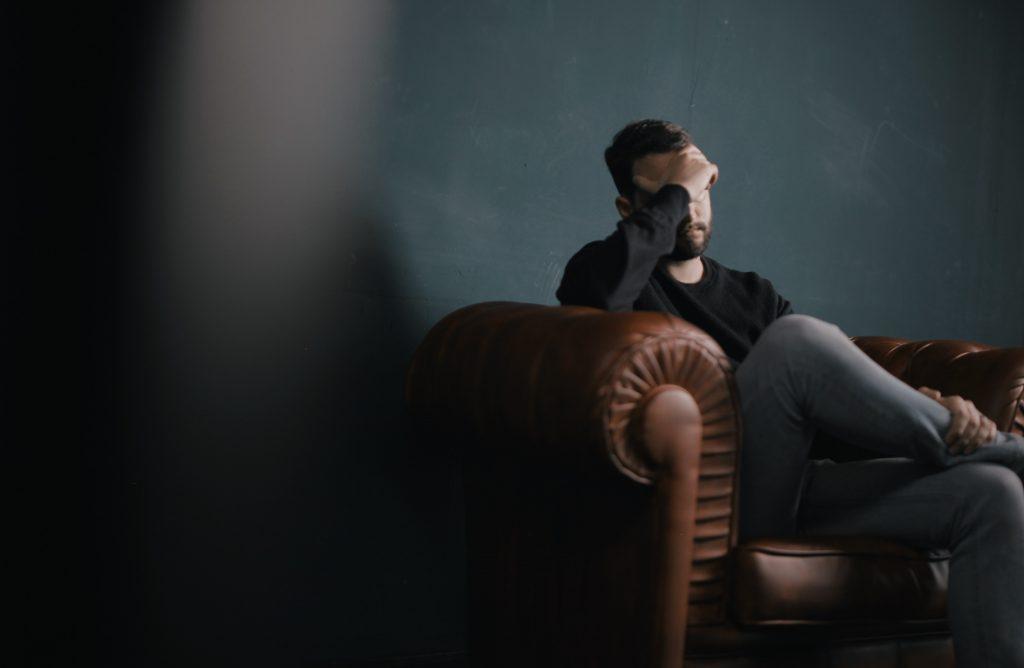 Man som sitter i sofaen bekymret