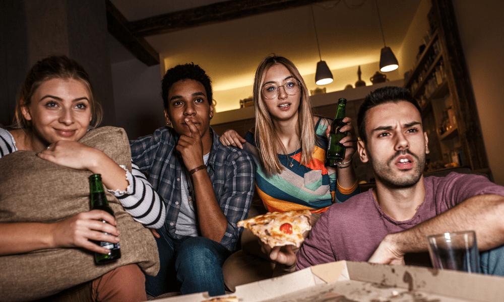 gruppe med fire personer som spiser, drikker og ser på tv
